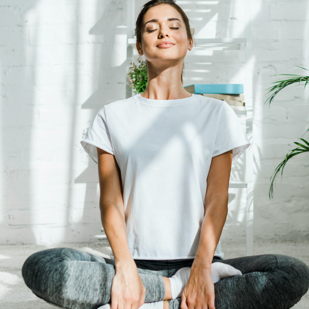 A smiling woman with her legs crossed in a yoga pose