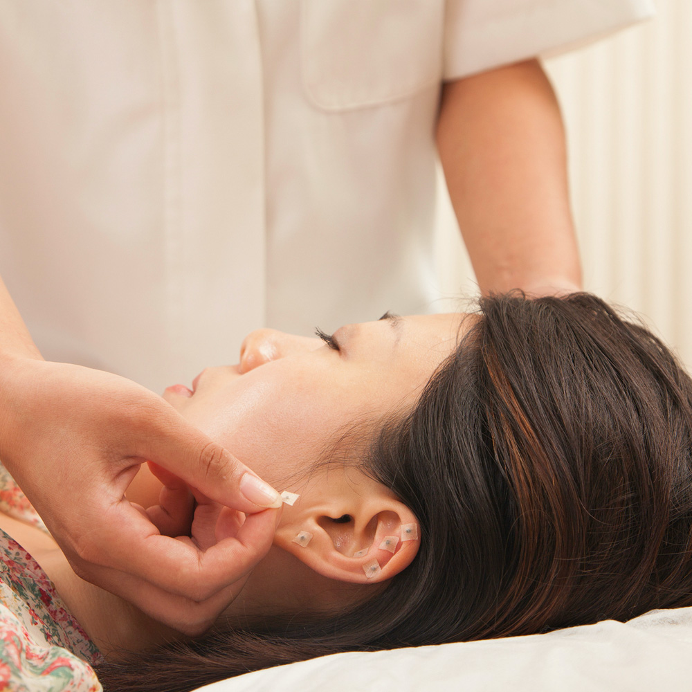 A refuge acupuncturist placing pins on a patient's earlobe