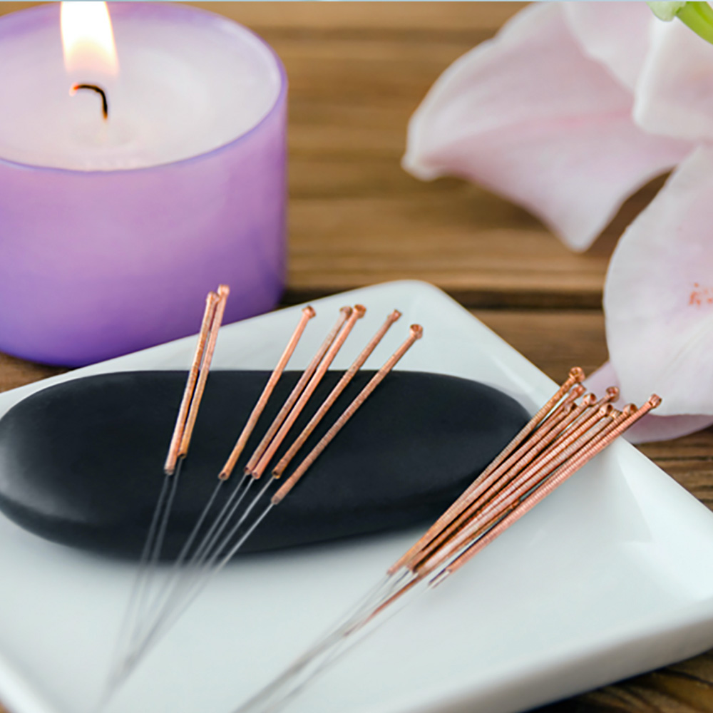 A lit candle is placed next to seven acupuncture pins
