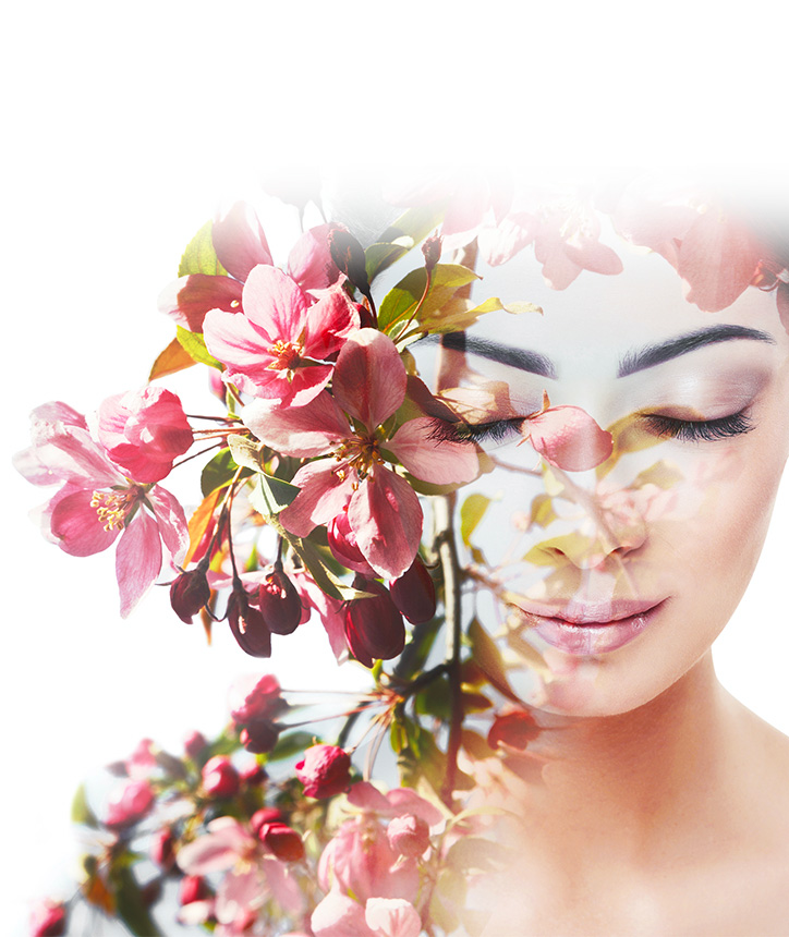 A woman looking downwards, holding a bough of flowers against her face