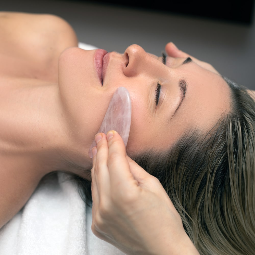 A flat stone being scraped against a patient's face during a gua sha facial.