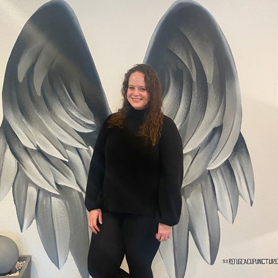 Clinical herbalist, dr. Catlin r dilli standing against a wall on which angel wings are depicted.
