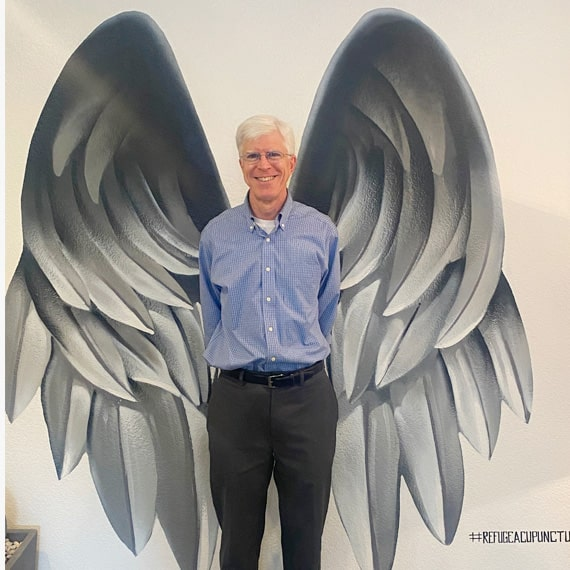 Clinical herbalist, michael harman standing in front of a wall on which angel wings are depicted.