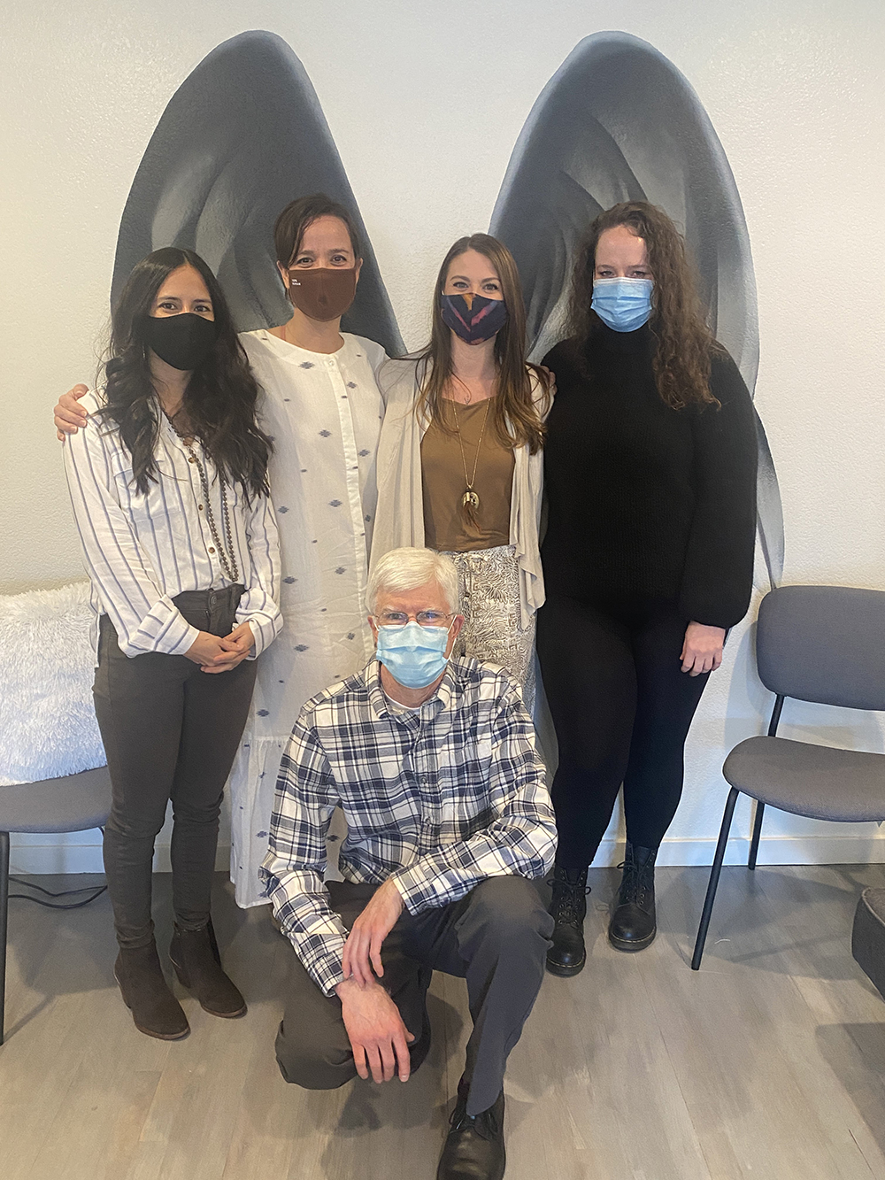 Patient specialists, lisa rundall, elena beltran, and kristin black, standing with michael harman and dr. Caitlin r. Dilli standing in front of a wall on which angel wings are depicted.